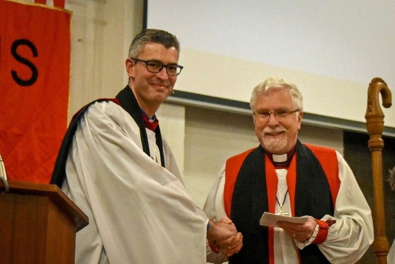 Jim congratulated by Bishop Harold