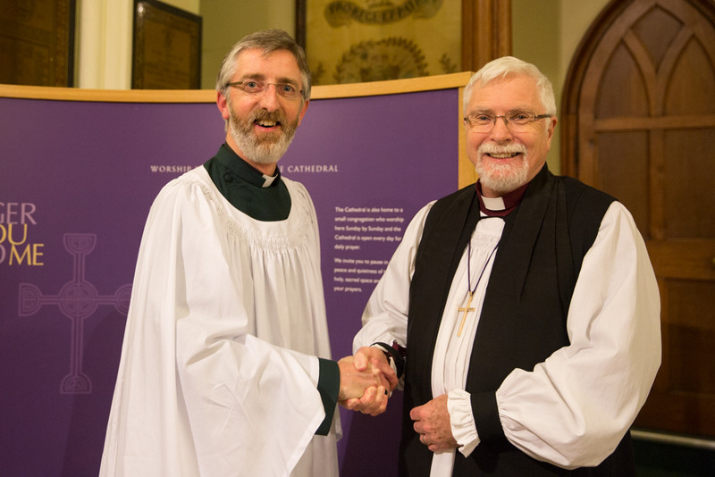 Canon John Auchmuty congratulated by Bishop Harold Miller